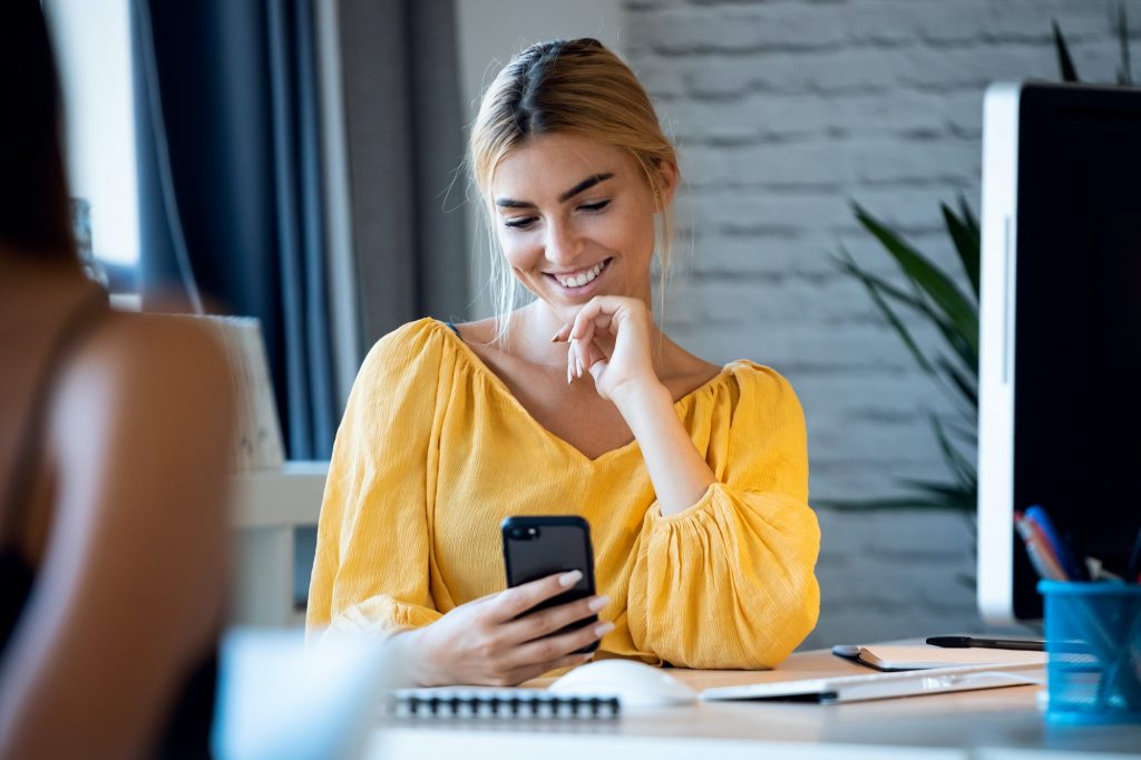 happy freelance business woman seller texting with her mobile phone